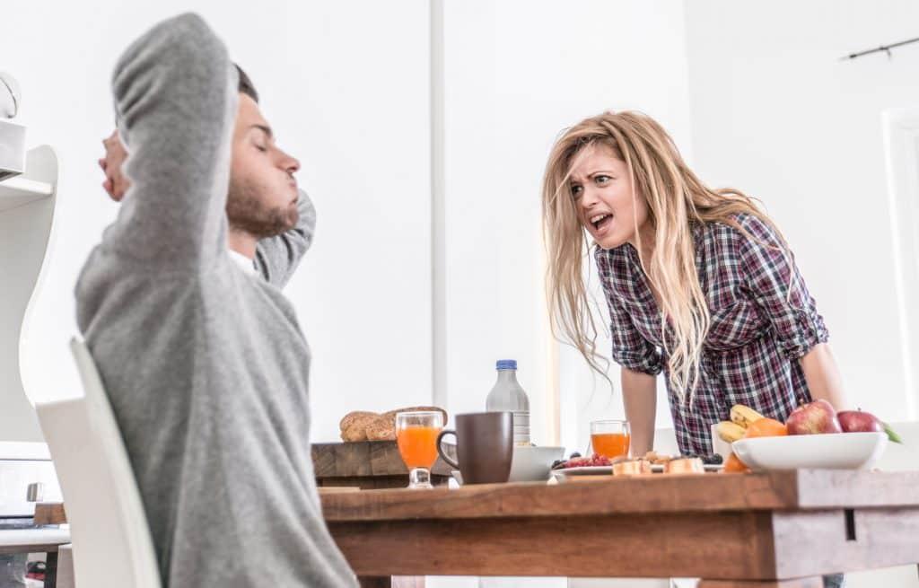 Mulher gritando com homem, que coloca as mãos atrás da cabeça, na mesa de café da manhã.