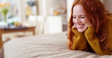 Mulher sorrindo deitada na cama com as mãos apoiando a cabeça
