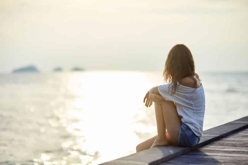Garota sentada em ponte olhando para o lago com sol ao fundo