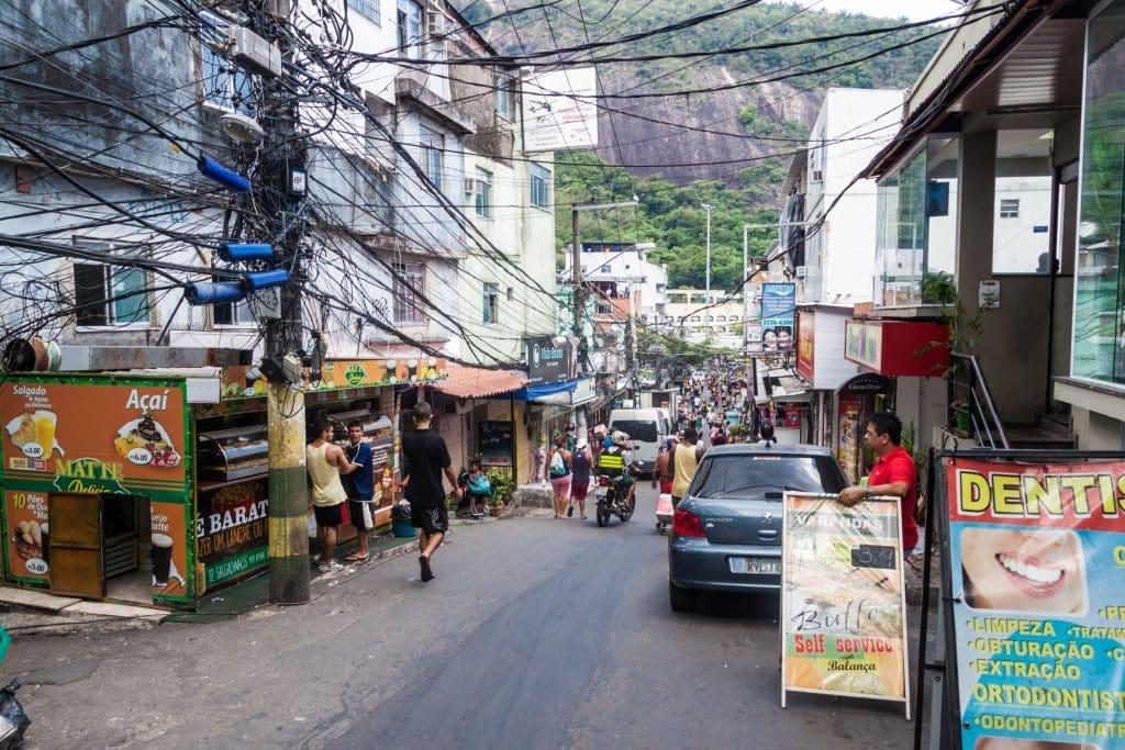 Rua em meio de favela, com muitas pessoas andando a pé.