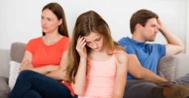Pais sentados no sofá descontentes com filha triste ao meio.