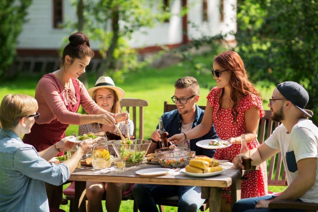 Grupo de pessoas comendo em uma mesa de madeira ao ar livre.