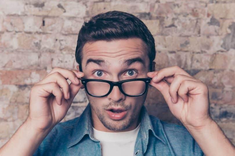 Homem com as mãos em óculos no rosto e expressão de surpresa