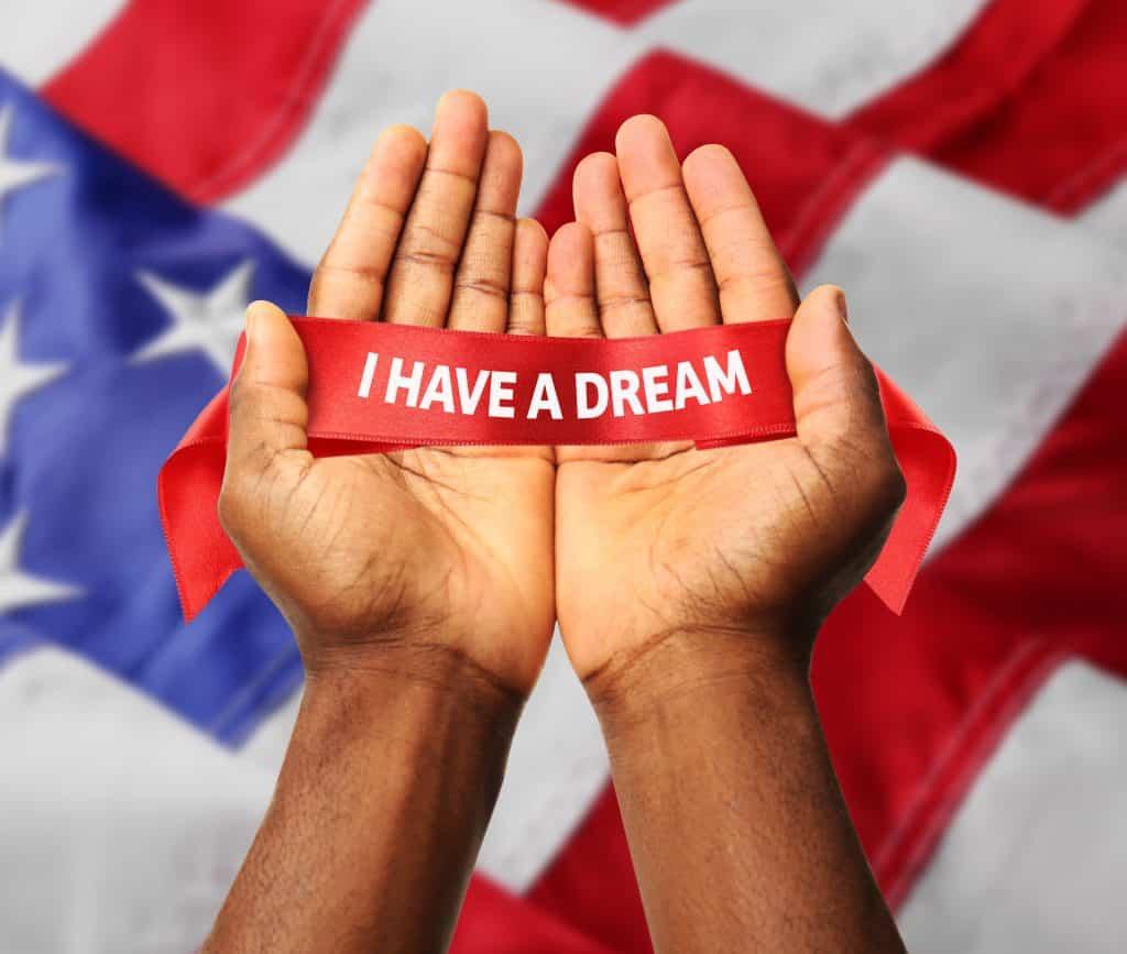 """Imagem das mãos de um negro e sobre elas uma fita vermelha com os dizeres escrito em branco: """"I Have a Dream"""" - """"Eu tenho um sonho"""". Ao fundo a bandeira dos Estados Unidos."""