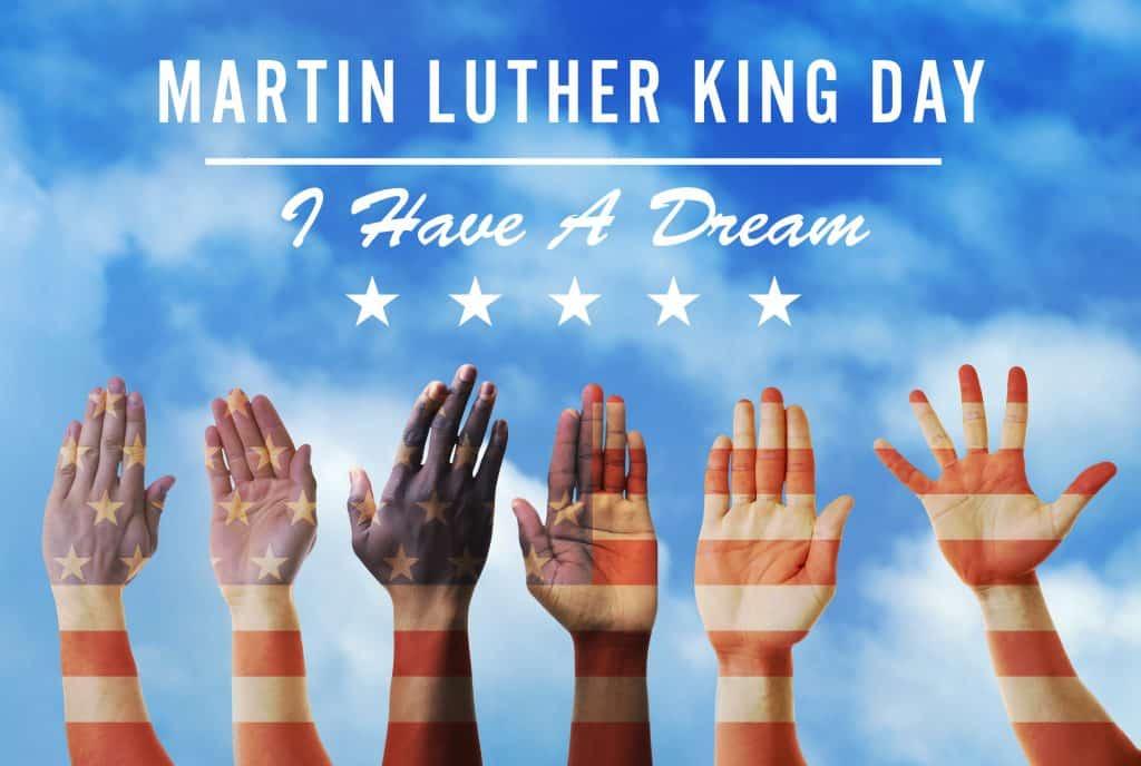 Imagem de várias braços erguidos. Eles estão pintados com as cores e os símbolos da bandeira dos Estados Unidos. Ao fundo a imagem do céu azul. Sobre ele a frase escrita: Dia de  Martin Luther King - Eu tenho um sonho.