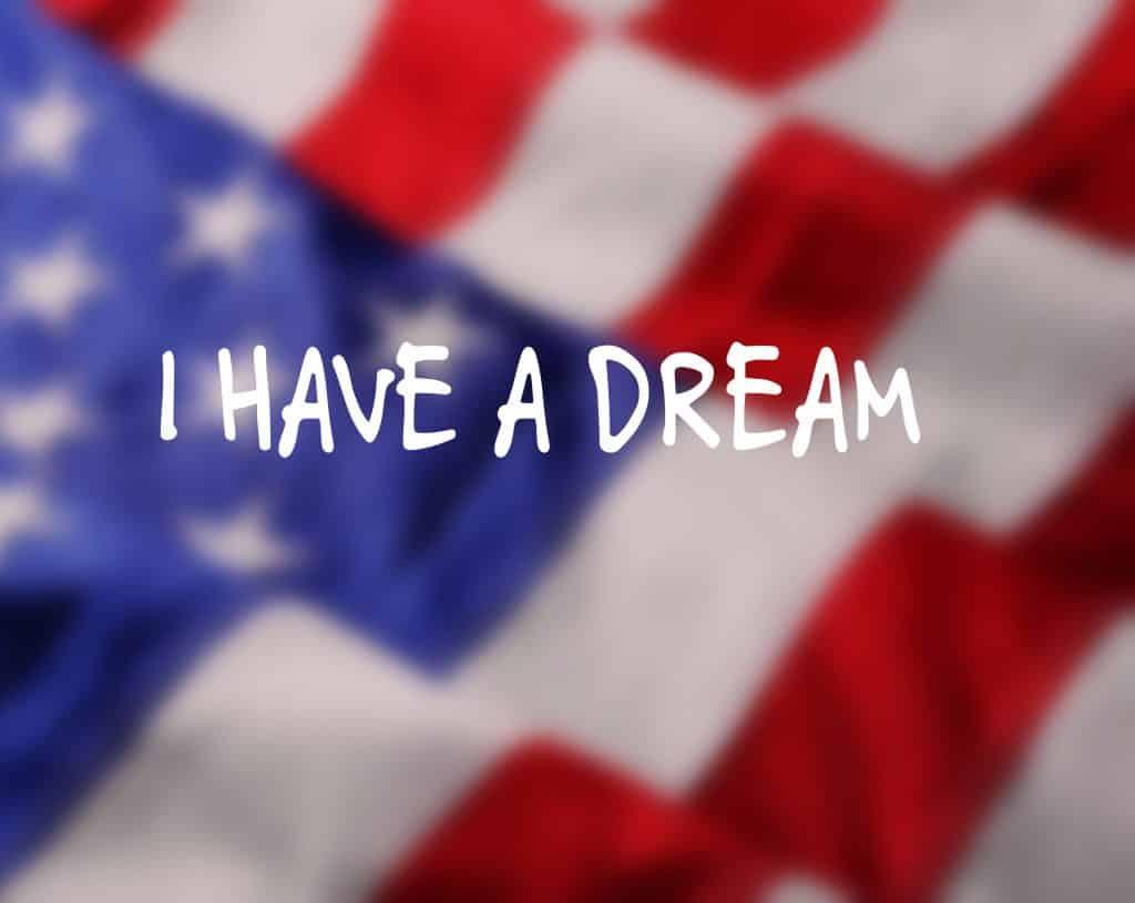 Imagem da bandeira dos Estados Unidos e sobre ela está escrita a frase de Martin Luther King: Eu tenho um sonho.