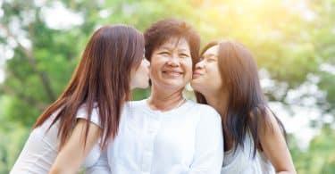 Duas mulheres beijando a mãe na bochecha, enquanto esta sorri.