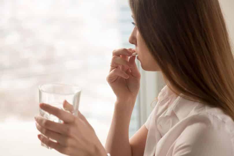 Mulher vista de perfil olhando por uma janela enquanto toma uma pílula de remédio junto a um copo d'água.