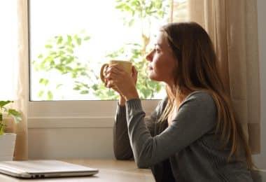 Mulher segurando uma xícara de chá e olhando para janela sentada em sua mesa da cozinha