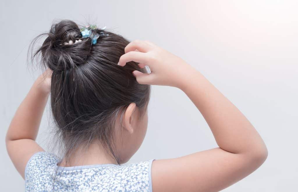 Imagem de uma criança de costas. Ela usa um coque na cabeça e está com as duas mãos coçando a cabeça.