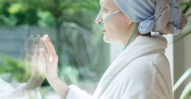 Mulher com câncer olhando pela janela