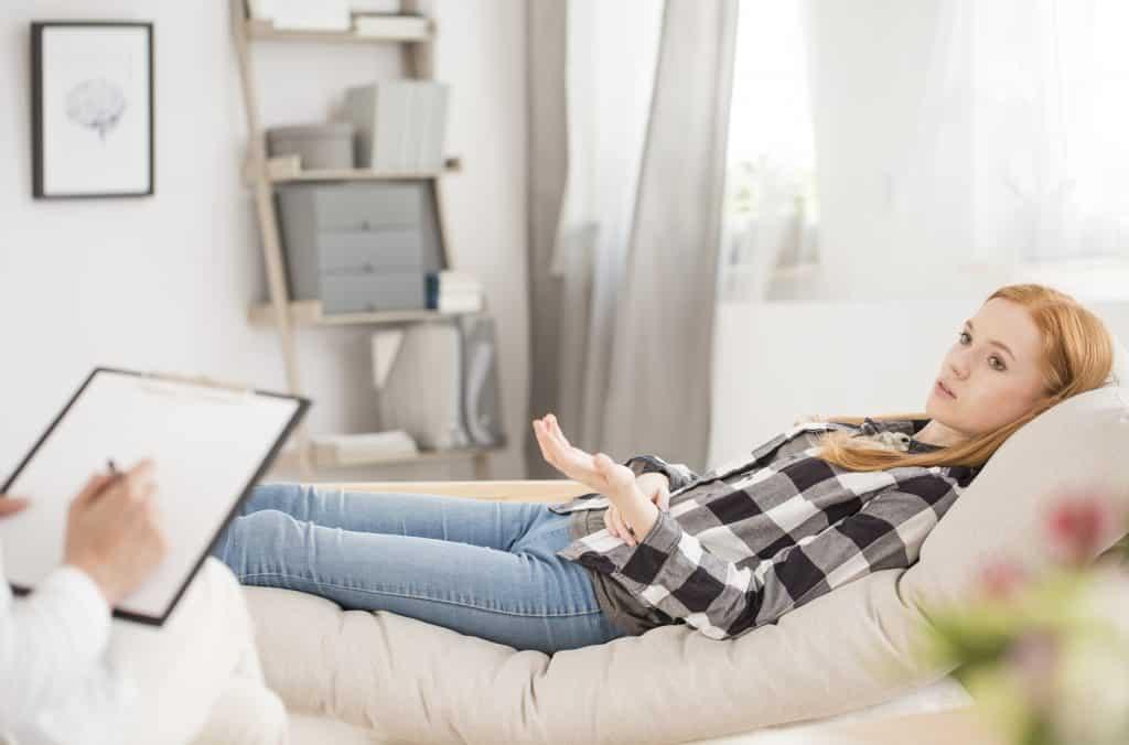 Imagem de uma mulher deitada em um divã fazendo uma sessão de terapia.