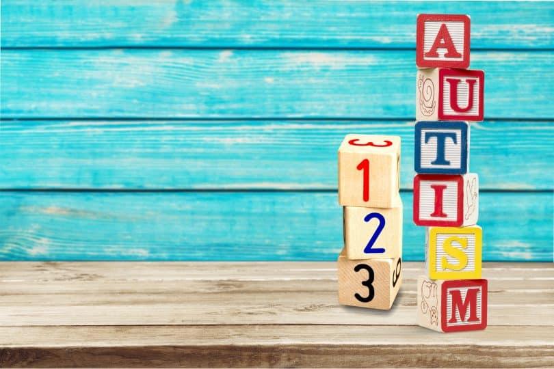 """Peças de madeira formando a palavra """"autism"""" e os números """"123""""."""