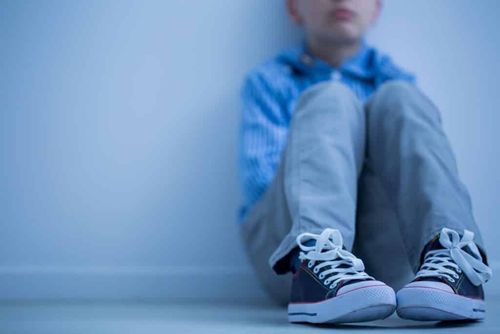 Imagem de um garoto autista - da boca para baixo. Ele está enconstado em uma parede branca. Ele veste uma camisa azul clara com listras brancas, calça cinza claro e um tênis azul jeans.