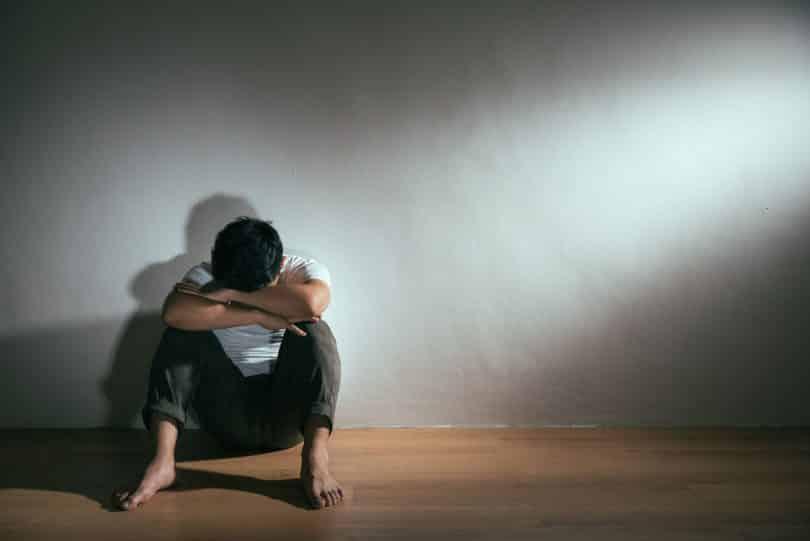 Homem sentado no chão, encostado em uma parede, com os joelhos flexionados e os braços apoiados neles. Ele esconde seu rosto apoiando a testa nos braços.