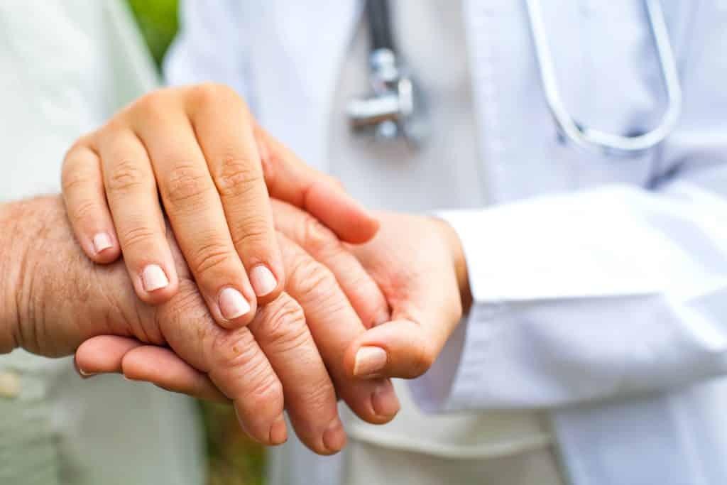 Imagem do jaleco branco de uma médica e suas mãos segurando as mãos de um paciente diagnosticado com parkinson.