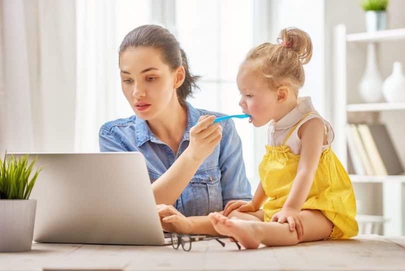 Mãe trabalhando com um computador em home office enquanto dá comida na boca de sua filha pequena, que senta em cima da mesa.