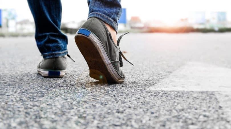 Pés andando com seta no chão apontando para frente