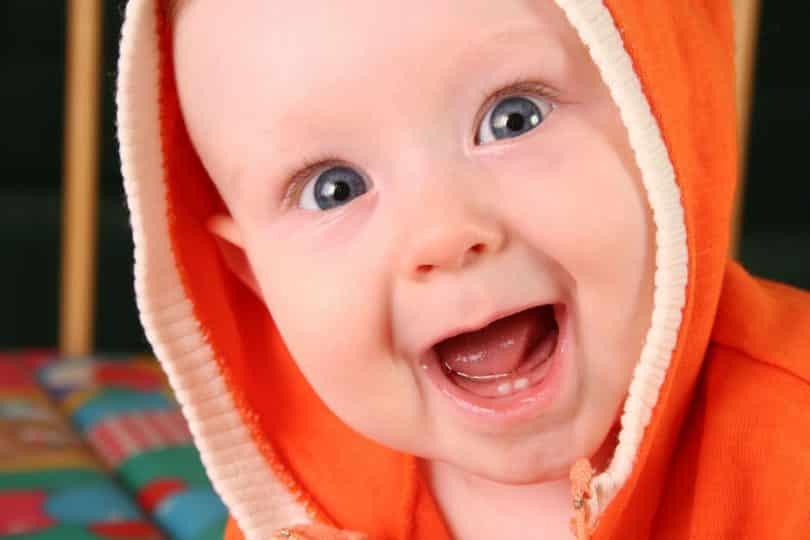 Bebê sorrindo com seus dois dentinhos aparecendo.