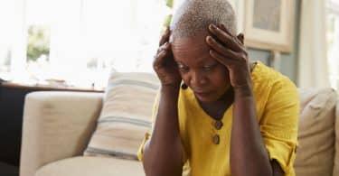 Mulher sentada em sofá com mãos na cabeça e cabisbaixa