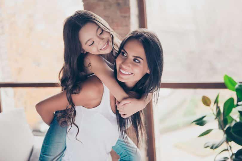 Mulher rindo e segurando menina pendurada em suas costas, que também ri.