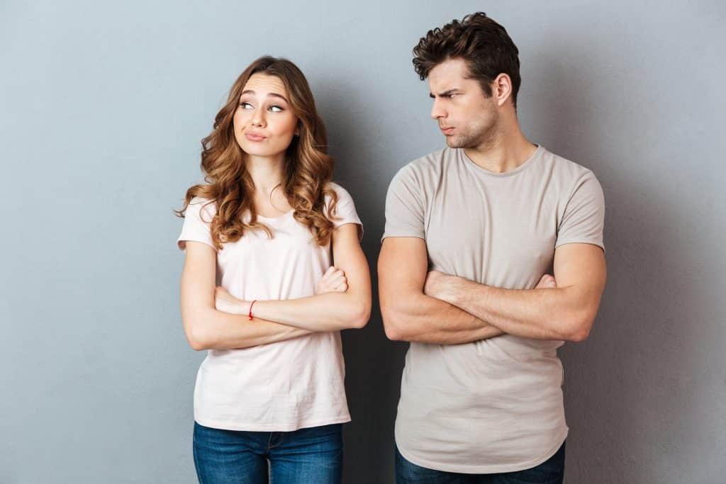 Imagem de um casal de homem e mmulher. Ambos vestem camiseta bege e calça jeans. O homem está olhando atravessando para a mulher que não está se importando com o que o homem está pensado.