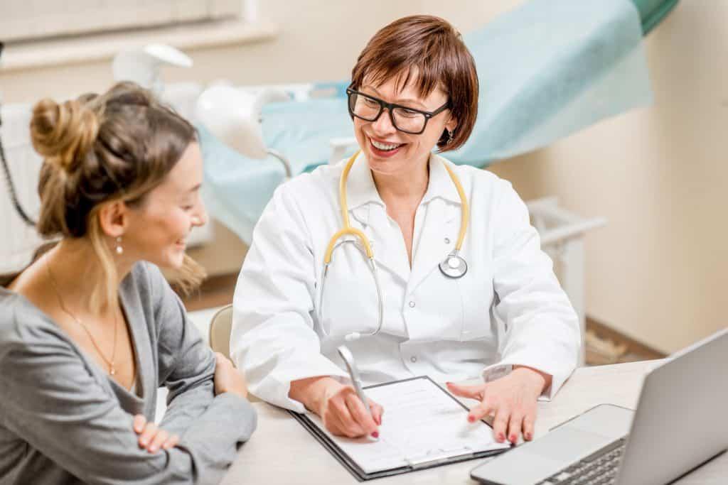 Mulher conversando com ginecologista no consultório