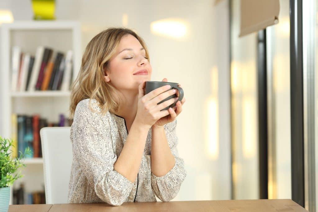 Mulher segurando uma xícara de olhos fechados em seu escritório de casa