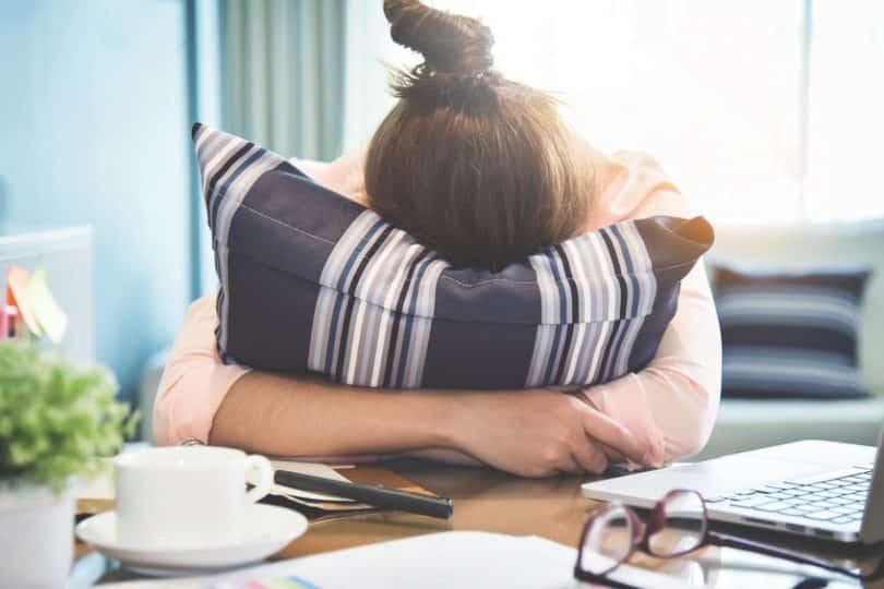 Mulher abraçando almofada em casa