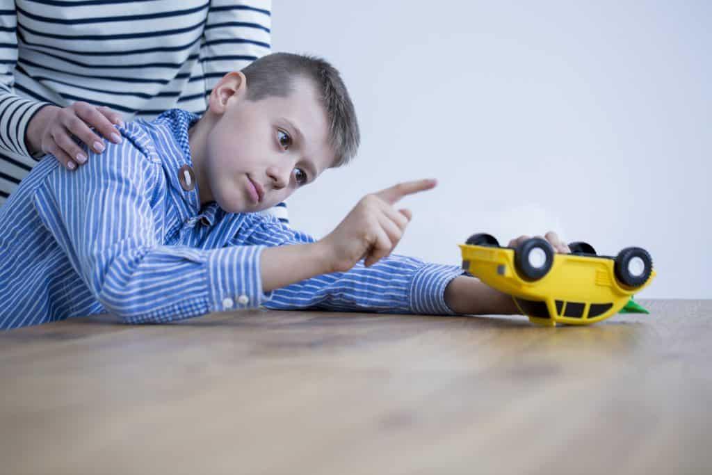 Imagem de um garoto olhando e apontando para o seu carrinho de brinquedo amarelo. Atrás dele, está a sua mãe colocando as mãos sobre os ombros.