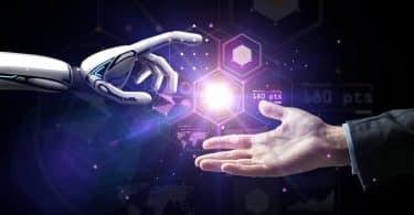 Mão robótica entrando na imagem pelo lado esquerdo, e mão humana entrando pelo lado direito. No centro, próximas de se encontrarem, luzes com pontos e linhas, simbolizando tecnologia, fica no meio das duas.