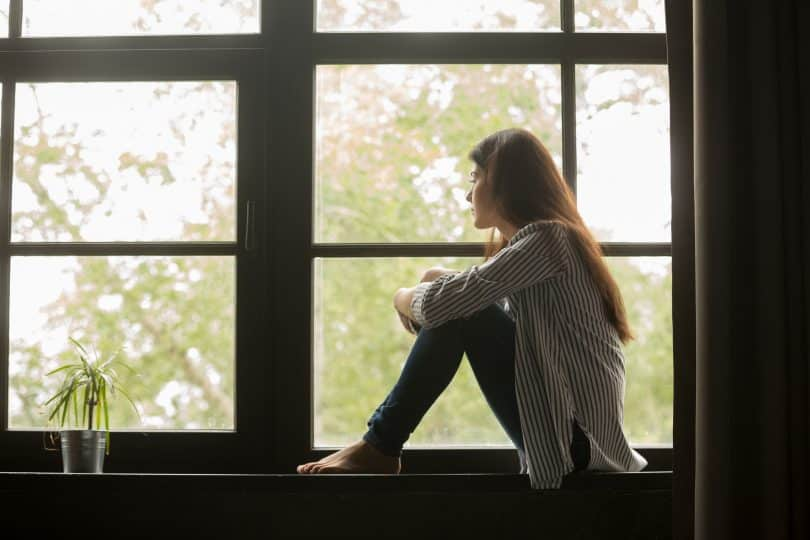 Mulher sentada na janela, olhando para fora, com as mãos segurando os joelhos.