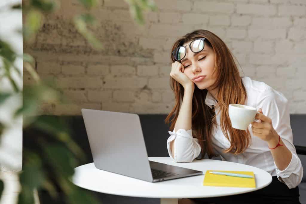 Mulher em frente a um computador, apoiando seu rosto em sua mão, e segurando uma xícara de café. Seus olhos estão fechados.
