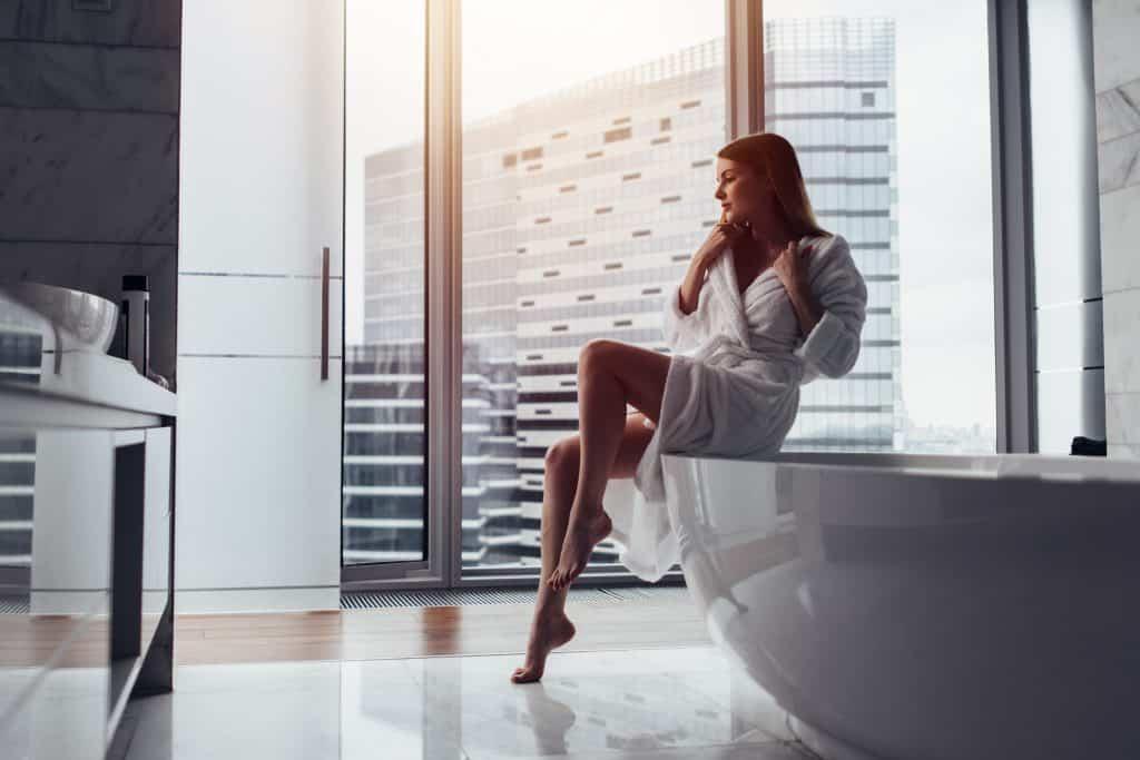 Imagem de uma linda mulher de cabelos longos. Ela usa um roupão de banho branco e está sentada na borda de uma banheira branca. Ao fundo a imagem de uma janela de vidro e um prédio ao fundo.
