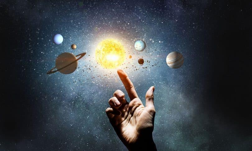 Desenho do sistema Solar pequeno, com um dedo humano tocando o Sol.