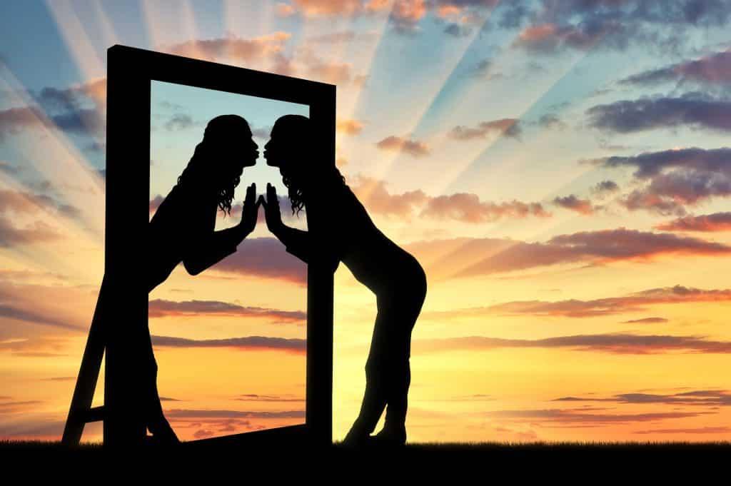 Silhueta de mulher e espelho em pôr-do-sol. A mulher está beijando seu reflexo no espelho, que faz o mesmo.