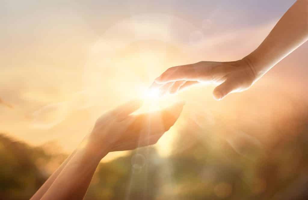 Duas mãos se tocando em meio a raios de luz.