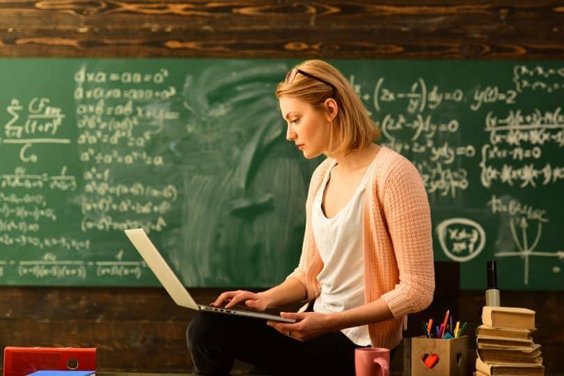 Professora sentada em sua mesa da sala de aula usando notebook