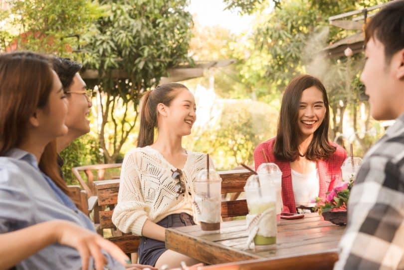 Grupo de pessoas sentadas ao redor de uma mesa com copos de suco vazios. Todos estão rindo.