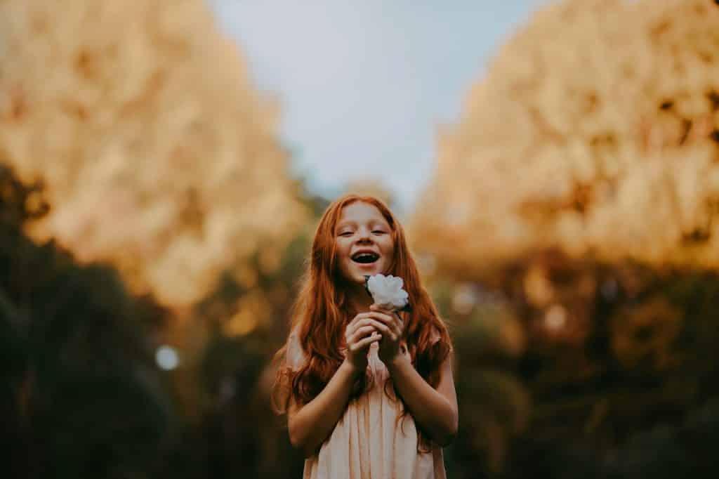 Menina em parque, segurando uma flor próxima ao seu rosto, e sorrindo com a boca aberta.