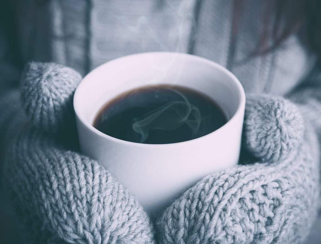 Mulher segurando xícara de chá com suas luvas