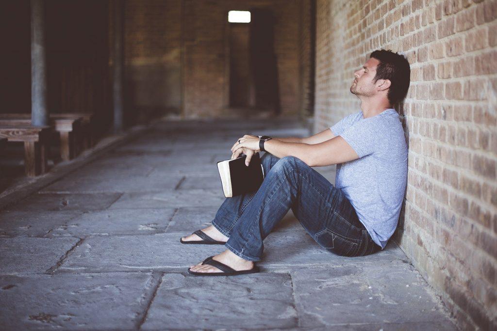 Imagem de um  homem sentado sozinho no chão, segurando entre as suas mãos um livro de capa preta. Ele está encostado em uma parede de tijolos e está pensativo.
