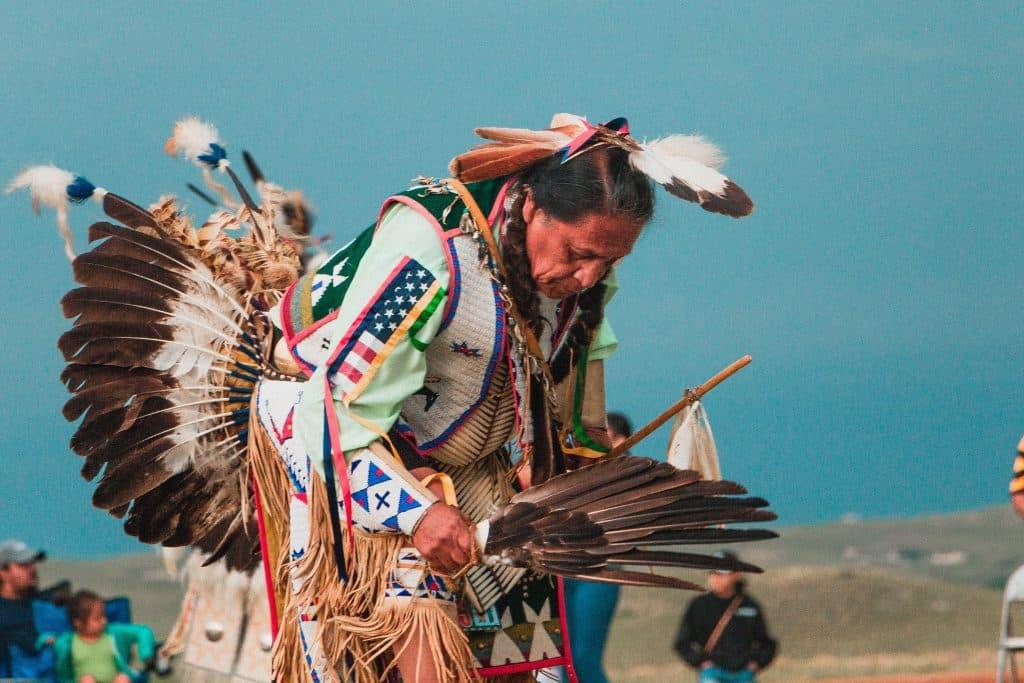 Índio com penas na mão.