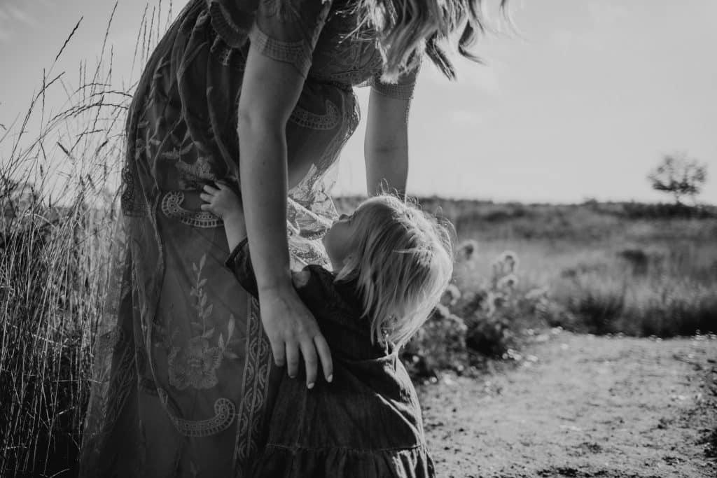 Mulher grávida de vestido pegando sua filha menor do colo, em um campo.