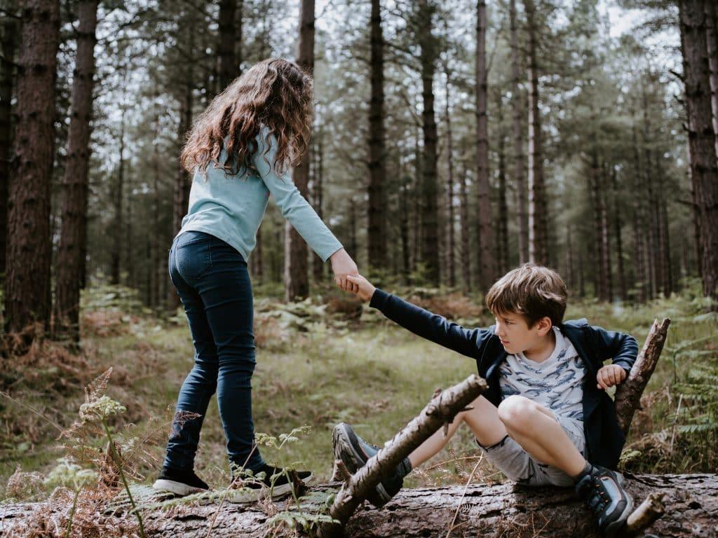 Menina ajudando menino que está caído no chão a levantar
