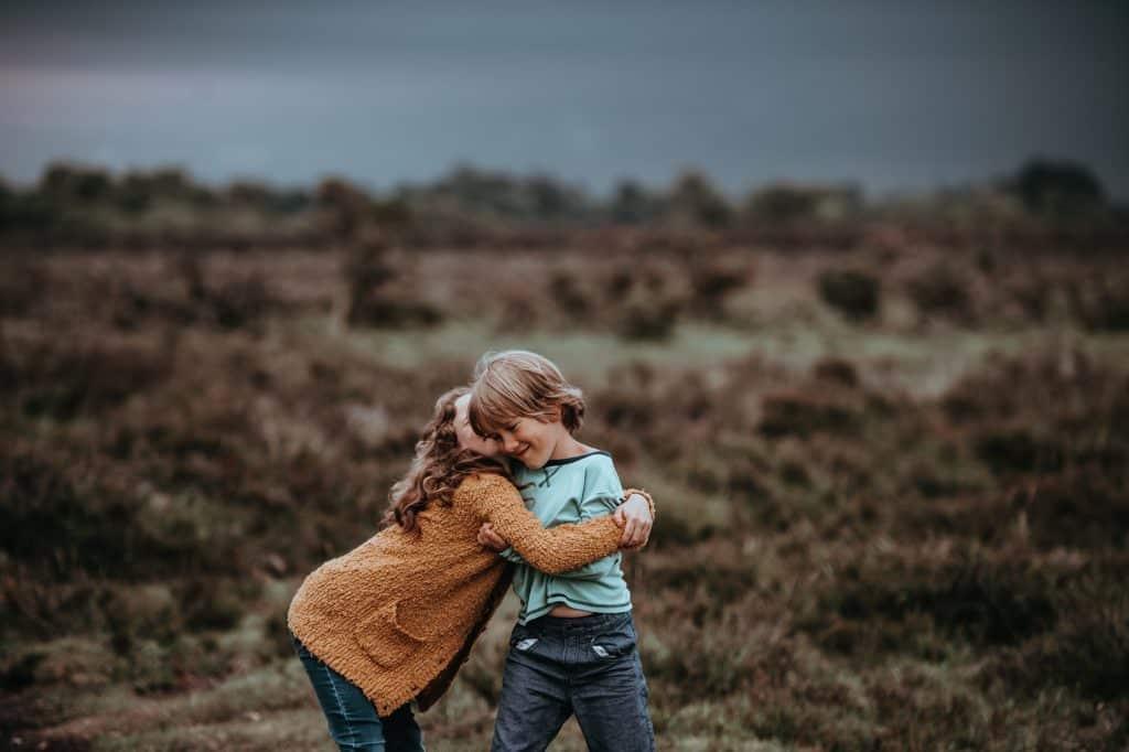 Duas crianças se abraçando em um local com gramado