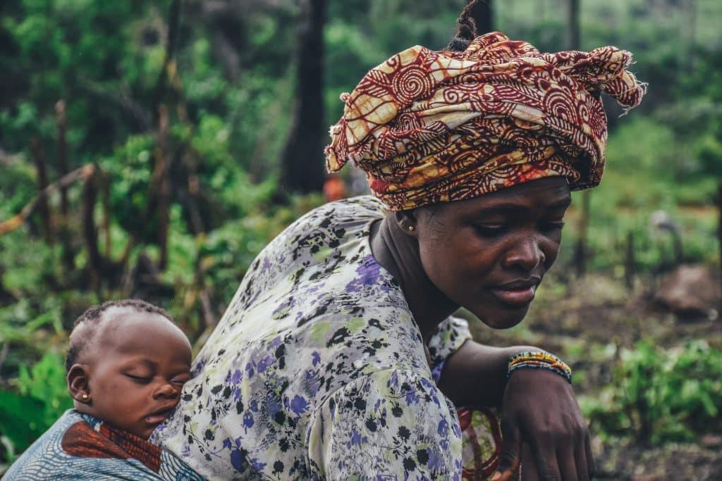 Mãe agachada com seu filho dormindo em suas costas. O bebê está preso por um pano.