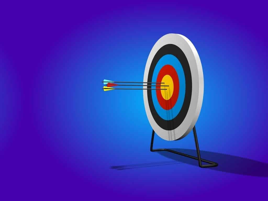 Imagem de tiro ao alvo, com três flechas dentro do arco central.