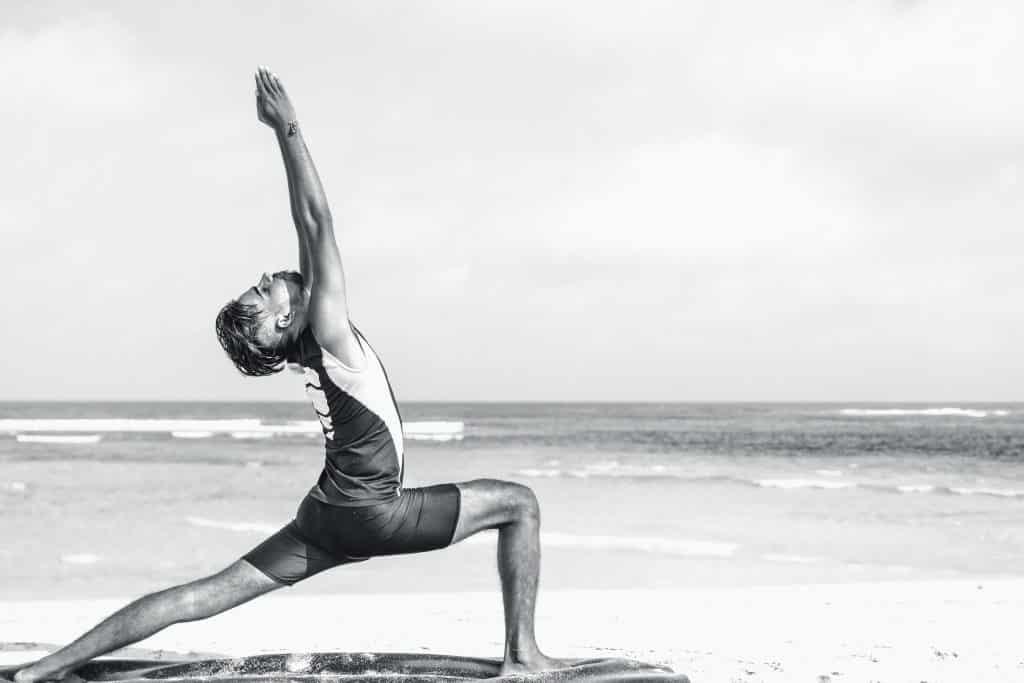 Homem na praia fazendo uma posição de yoga.