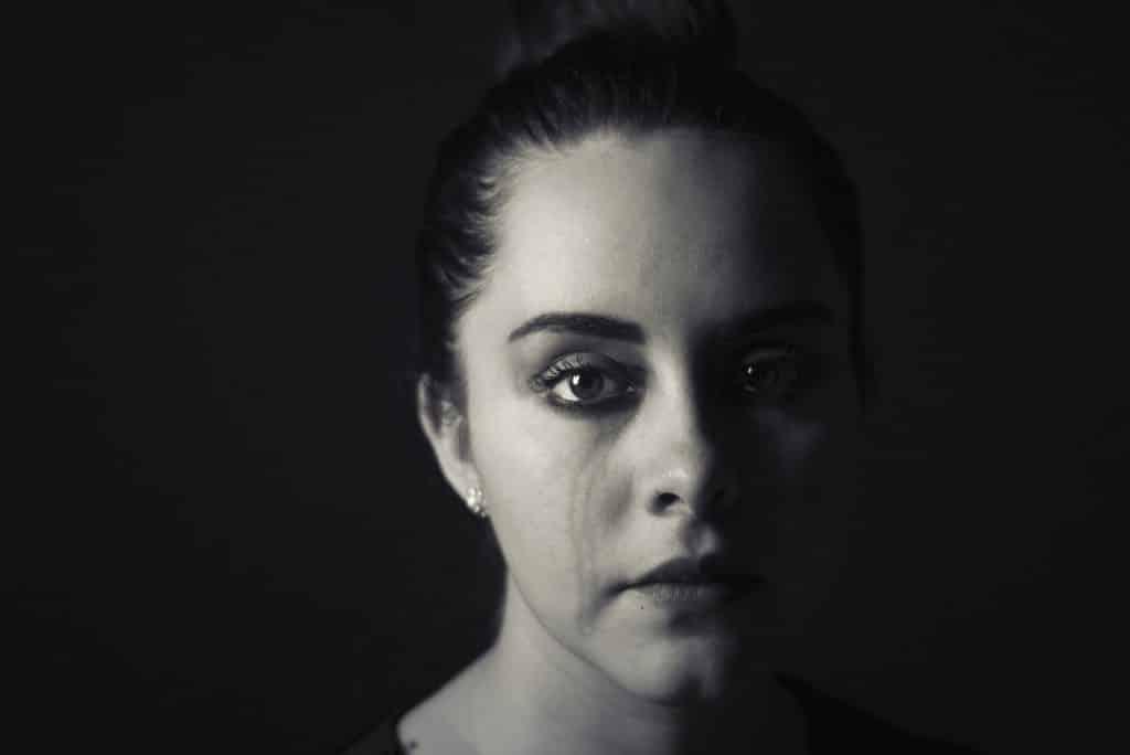 Imagem preto e branco de uma mulher com cabelo preso e marcas de lágrimas escorridas no rosto.